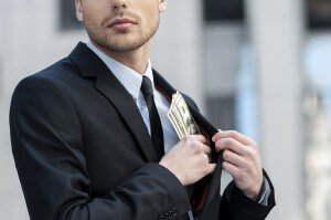 Pocketing company money. Cropped shot of a businessman placing money into his pocket